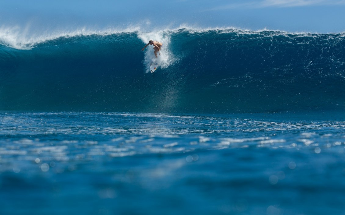 the girl is surfing on a big wave