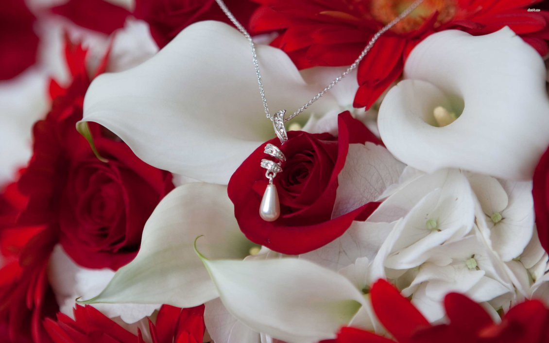 A Necklace With A Pearl On The White And Red Flowers