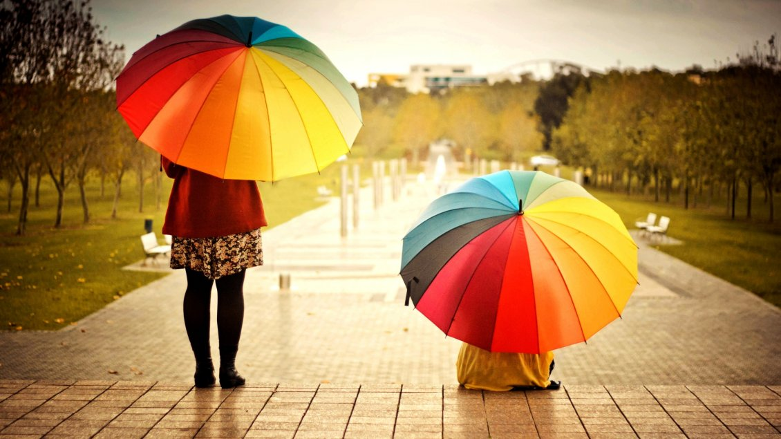 Two Women With Colorful Umbrellas In The Rain