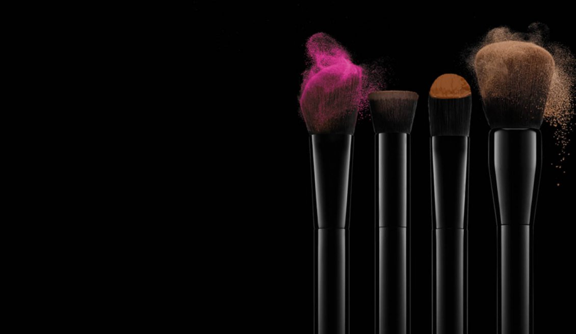 Brushes with coloured make-up on a dark background