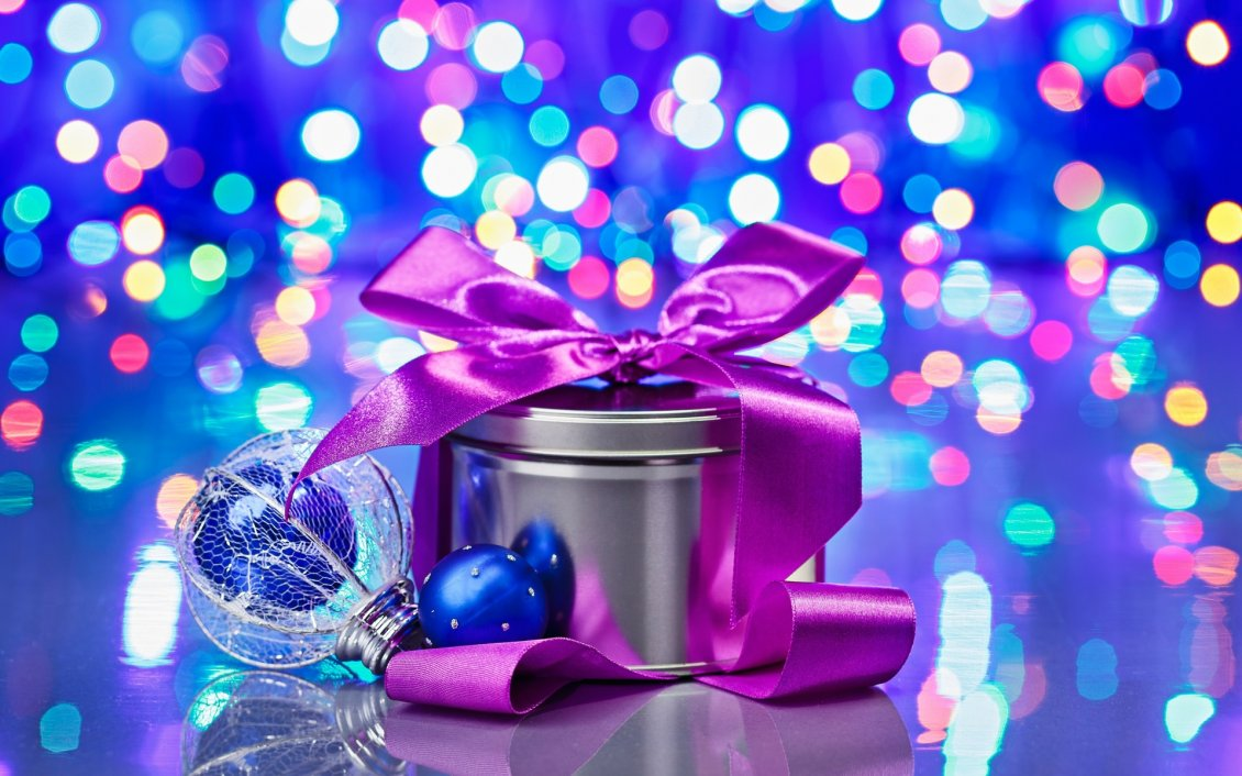 purple ribbon on a christmas gift lights on background