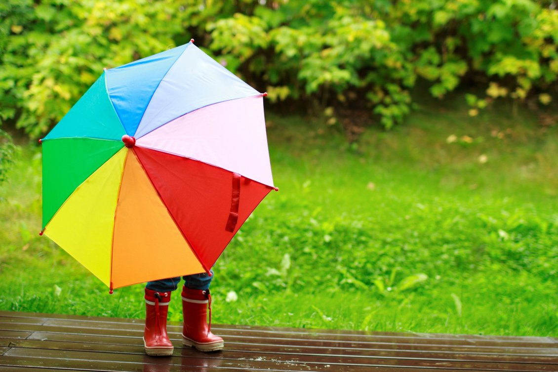 Download Wallpaper Little kid is playing in the rain with a colorful umbrella