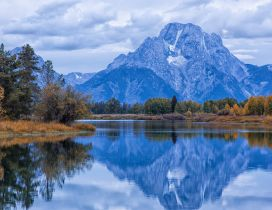 Montains, clouds and trees reflected in water