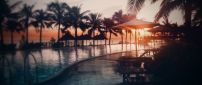 Sunset at the seaside, palms and swimming pool