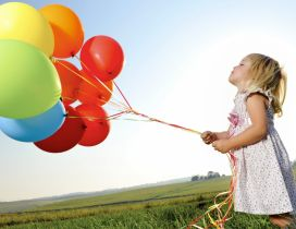 The girl with many colorful balloons in the grass
