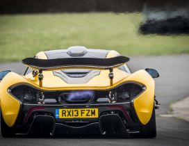 Yellow McLaren P1 exhaust flames