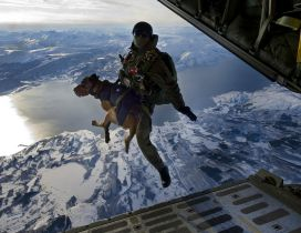 Soldier jumps from an airplane with a dog in her arms