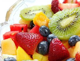 Colorful fruit salad in glass bowl