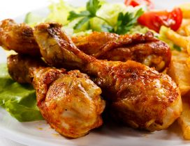 Chicken drumsticks and fries with salad and tomato