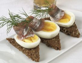 Three pieces of fish with boiled eggs on a plate