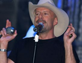 Bruce Willis at the microphone with a hat on the head