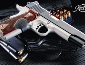 Gray Kimber gun and a a box with bullets
