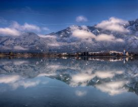 The city and mountains reflected in the lake waters