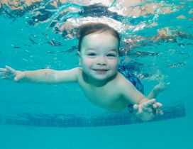 A cute baby swimming under water