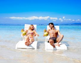 A couple relaxes on the sunbed in water