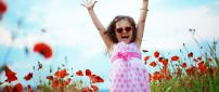 Happy baby girl in white and pink dress on the poppies field