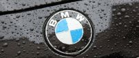 The BMW logo on a black car with raindrops