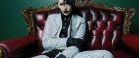 Marilyn Manson in a suit with stripes on the red sofa