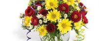 Bouquet of red, yellow and white flowers in the glass vase
