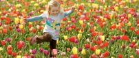 A happy girl in a field with colorful tulips