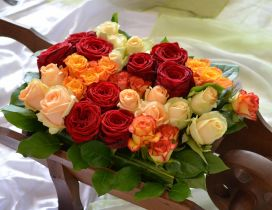 A wooden wheelbarrow full of colored roses