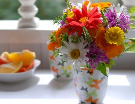 Many different colored flowers in a cup on the table