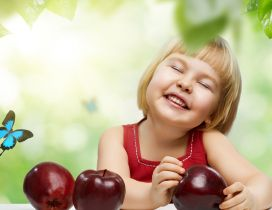 A sweet girl with a smile on face and with three red apples