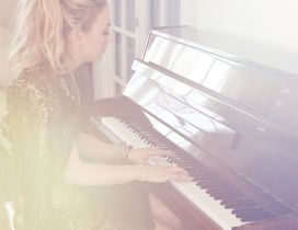 Emily Kinney, an American actress, playing the piano