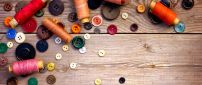 Threads and buttons in many colors on the wood