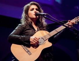 Katie Melua sings with a guitar on a scene