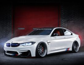 A beautiful white BMW F82 M4 in a garage