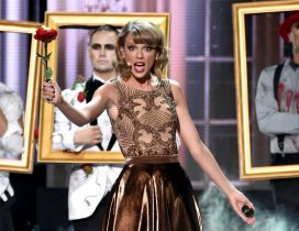 Taylor Swift sings on scene with a red rose in hand
