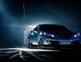 Blue Hyundai Genesis Coupe in a dark space