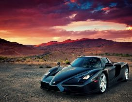 Black Enzo Ferrari in mountains in sunset