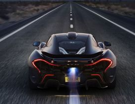 Black McLaren P1 on road, back view