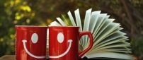 Two red cups with white smiles and a book