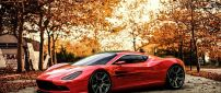 Red Aston Martin in a park in a autumn day