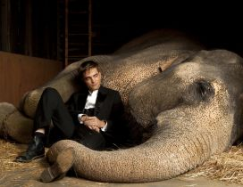 Robert Pattinson in black suit besides an elephant