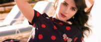 Emma Roberts in a black dress with red spheres