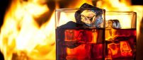Two glasses of whiskey with ice - fire on background