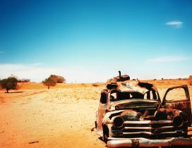 Old and very rusty classic car in the dessert