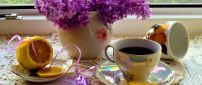 Lilac flowers and a delicious cup of tea with lemon