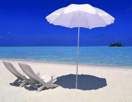 Two white sunbed and an umbrella - summer time