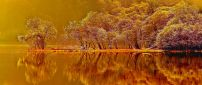 Amber Autumn nature - mirror in the lake at sunset