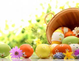 Wooden basket full with Easter eggs - Spring colours