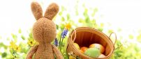 Funny rabbit and a basket with coloured Easter eggs