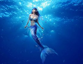 Beautiful blue mermaid in the middle of the ocean water