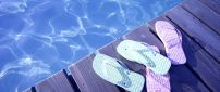 Blue and pink flip flop near the pool - Summer time