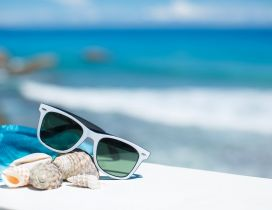 Sunglasses and shells -Wonderful blurry ocean on background