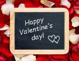 Happy Valentine's Day write on a blackboard - rose petals